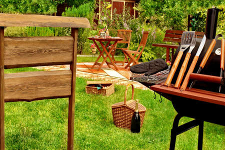 garden furniture: BBQ Grill, basket, hamper, wooden furniture, signboard in the summer Backyard garden. Party scene. Stock Photo