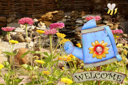 bee garden: Metal se�al de bienvenida con regadera y la abeja. Jard�n en el fondo.