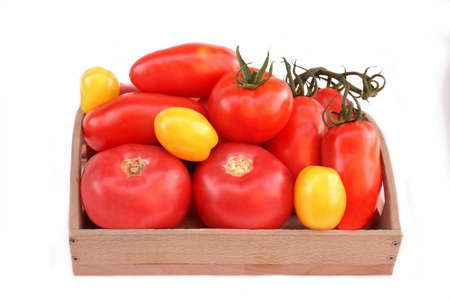 Different colors and size Tomatoes in wooden box isolated on white background photo