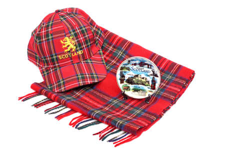 Scottish Red tartan cap, tartan scarves and souvenir plate Isolated on White photo