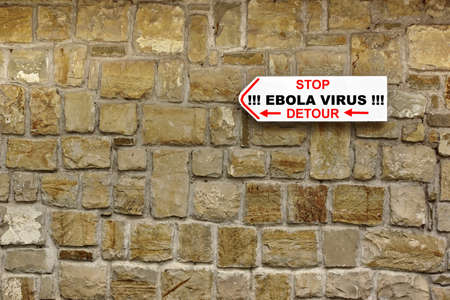barring: Direction Signboard with text STOP EBOLA VIRUS DETOUR on the old stone wall Stock Photo