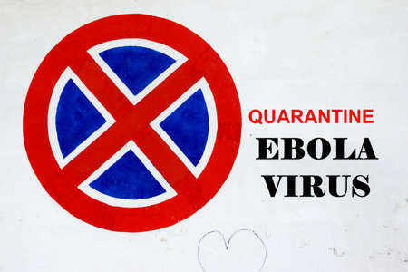 barring: White Wall with Signpost and text QUARANTINE EBOLA VIRUS Stock Photo