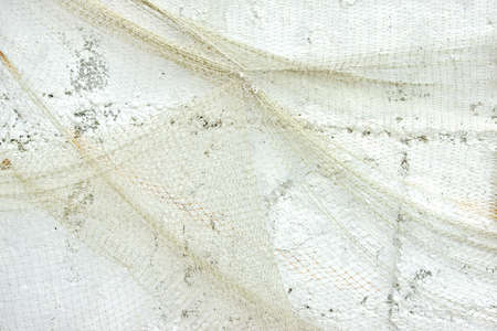 Old Fishing Net on White Wall Background photo