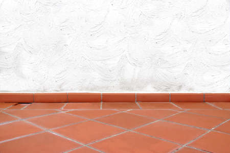 brush tailed: Terracotta Tailed Floor and White Concrete Wall with Brush Strokes Abstract Pattern.