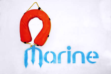 emergency vest: Life Vest and Marine Sign on White Concrete Wall. Background with space for text or image