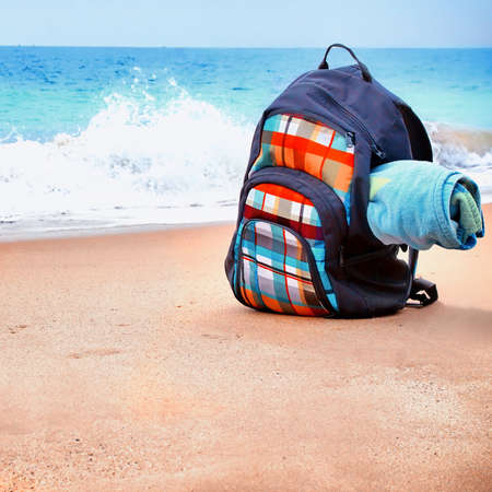 mochila de viaje: Mochila de viaje con la toalla en la playa del mar de verano. Alquileres de vacaciones y S�mbolo Foto de archivo