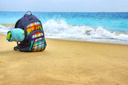 duffel: Travel Backpack with Towel on Summer Sea Beach. Holiday and Vacation Symbol Stock Photo