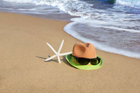 Straw Hat, Sunglasses and  Starfish on the Empty Sea Beach. Concept of summer accessories with sea water as background. photo