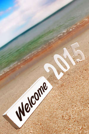 2015 New Year numbers on the sea beach and sign WELCOME. Background and Texture for text or image photo