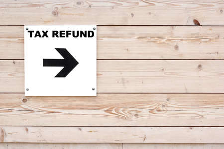 TAX REFUND Black Sign on Whiteboard. Timber White Wall in Background 版權商用圖片