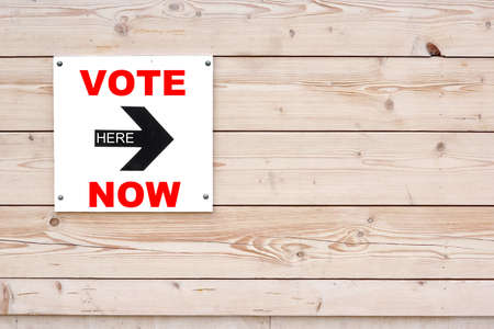 i voted: VOTE NOW HERE Black Sign on Whiteboard. Timber White Wall in Background Stock Photo