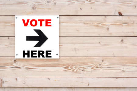i voted: VOTE HERE Black Sign on Whiteboard. Timber White Wall in Background