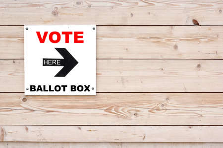 mayoral: VOTE BALLOT BOX HERE Red Black Sign on Whiteboard. Timber White Wall in Background