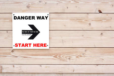 not give: DANGER WAY START HERE TO BE OR NOT TO BE Black Sign and Arrow on Whiteboard. Timber White Wall in Background Stock Photo