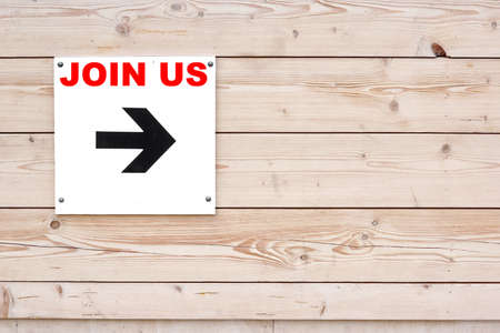 JOIN US Black Sign and Arrow on Whiteboard. Timber White Wall in Background photo