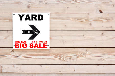 YARD BIG SALE Sign with Arrow on Timber Wall. Here Sign on Black Arrow.  Two small red sign ONE DAY, BEST PRICE photo