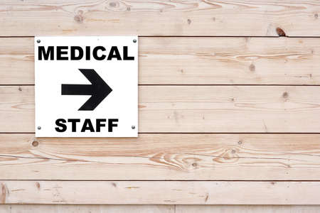 MEDICAL STAFF Black Sign and Arrow on Whiteboard. Timber White Wall in Background photo