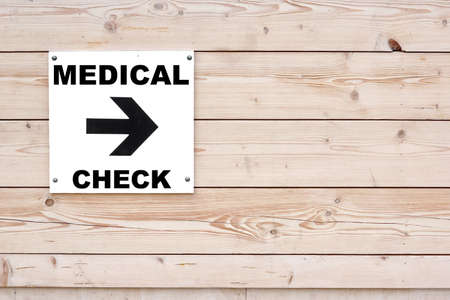 MEDICAL CHECK Black Sign and Arrow on Whiteboard. Timber White Wall in Background photo