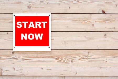START NOW Red White Sign on Timber Wall Background photo
