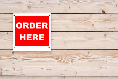 closeout: ORDER HERE. Red White Sign on Timber Wall Background