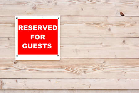 booked: RESERVED FOR GUESTS Red White Sign on Timber Wall Background