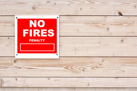 no fires: NO FIRES PENALTY Red White Sign on Timber Wall Background