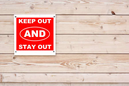 keep out: KEEP OUT AND STAY OUT Red White Sign on Timber Wall Background Stock Photo