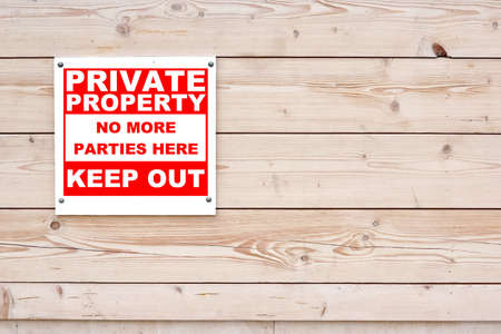 keep out: PRIVATE PROPERTY NO MORE PARTIES HERE KEEP OUT Red White Sign on Timber Wall Background Stock Photo