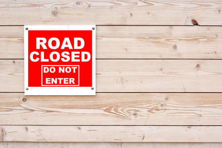 road closed: ROAD CLOSED DO NOT ENTER Red White Sign Red White Sign on Timber Wall Background Stock Photo