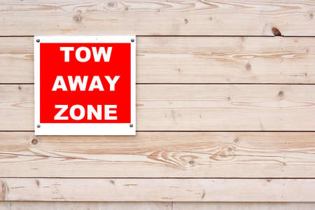 visitors area: TOW AWAY ZONE Red White Sign on Timber Wall Background