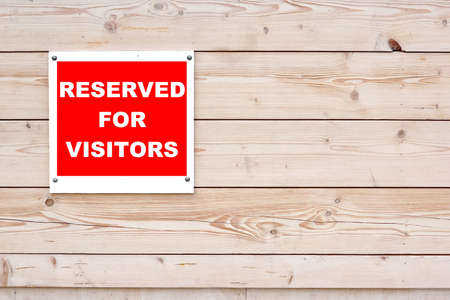 RESERVED FOR VISITORS Red White Sign on Timber Wall Background photo