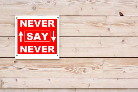 NEVER SAY NEVER Red White Sign on Timber Wall Background photo