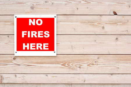 no fires: NO FIRES HERE Red White Sign on Timber Wall Background