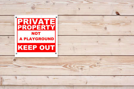 keep out: PRIVATE PROPERTY NOT A PLAYGROUND KEEP OUT Sign Red White Sign on Timber Wall Background