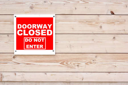do not enter: DOORWAY CLOSED DO NOT ENTER Red White Sign Red White Sign on Timber Wall Background Stock Photo