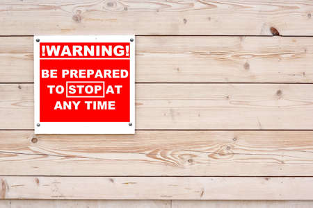 be alert: WARNING BE PREPARED TO STOP AT ANY TIME Red White Sign on Timber Wall Background