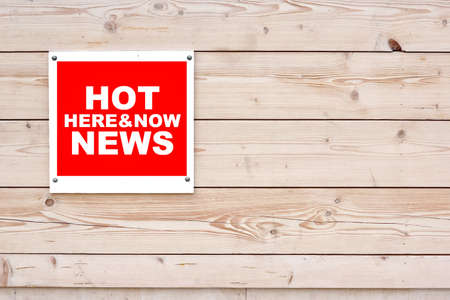 hot news: HOT NEWS HERE AND NOW Red White Sign on Timber Wall Background Stock Photo