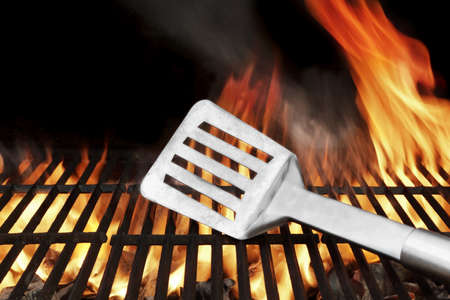 Spatula on the BBQ Hot Grill. Flames of Fire on the Background photo