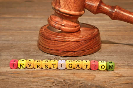 Sign INVESTIGATION and Gavel on Wooden Table