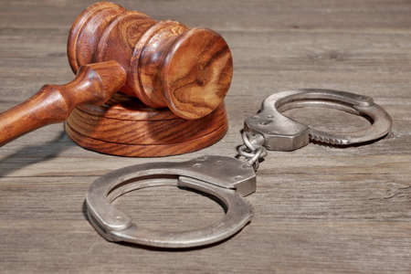 restraints: Handcuffs and Gavel in Courtroom on Wooden Table Stock Photo