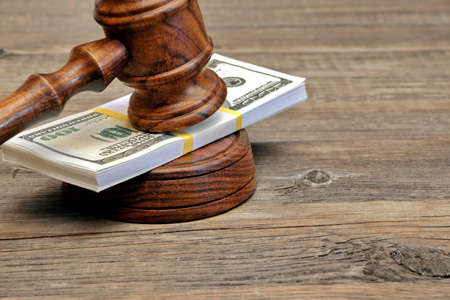 Wad of Money and Judges Gavel on Wooden Table photo