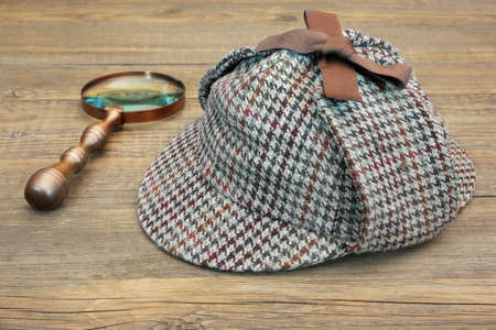 Hat or  Deerstalker Hat and Retro Magnifying Glass on Wooden Table Stock Photo