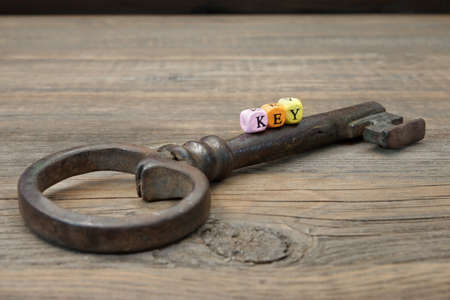 passkey: Old Rusty Iron Key and Sign KEY on a Wooden Background