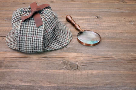 glass table: Deerstalker or Sherlock Hat and magnifying glass on Old Wooden table
