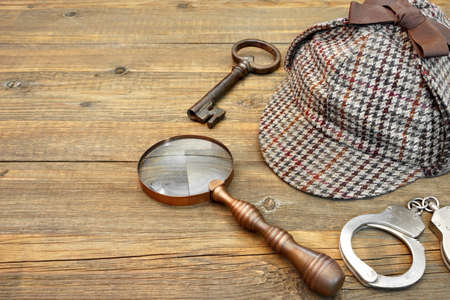 Cap famous as Deerstalker, Old Key, Real Handcuffs and Vintage Magnifying Glass on Grunge Wooden Table