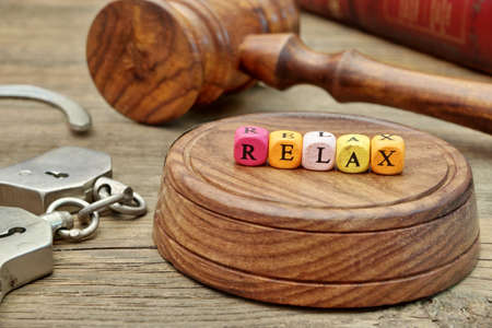 manacle: Sign Relax, Judges Gavel and Soundboard, handcuffs and book on Grunge Wooden Table Stock Photo