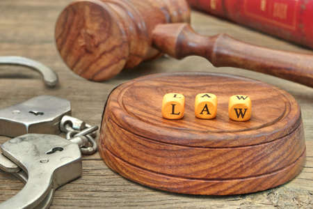 soundboard: Sign LAW on the Soundboard, Judges Gavel, handcuffs and book on Grunge Wooden Table Stock Photo