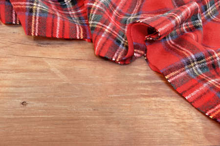 scarves: Traditional Scottish Red Tartan  Woolen Soft and Worm Scarf on Grunge Timber Board. Background with Free Space.