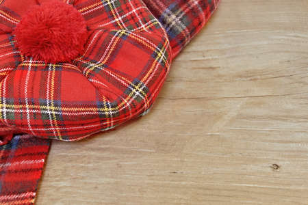 neckwear: Traditional Scottish Red Tartan Bonnet and Scarf Men headgear and neckwear on Grunge Timber Board. Background with Free Space. Stock Photo