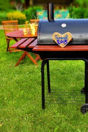 friend nobody: BBQ Party Sign on Wooden Heart at Barbecue Appliance on the Backyard at Summertime. Outdoors Furniture on the background. Stock Photo
